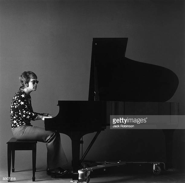Fulllength portrait of Britishborn musician Elton John playing a black grand piano while wearing sunglasses a longsleeved shirt covered in stars and...