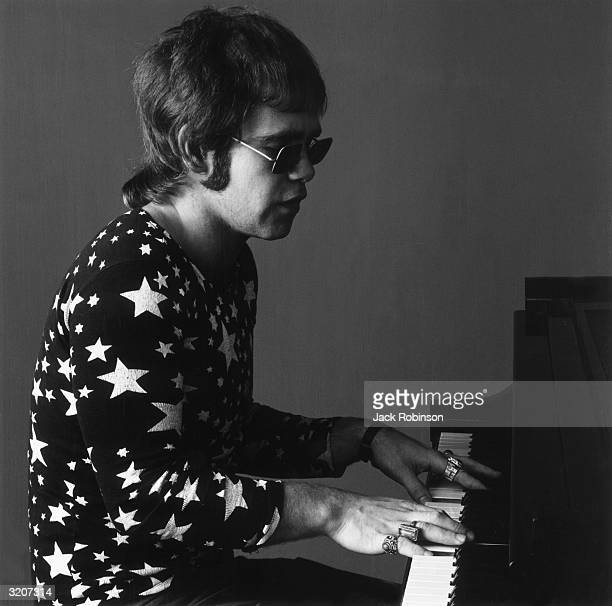Portrait of Britishborn musician Elton John playing the piano and singing John wears sunglasses a longsleeved shirt covered in white stars and many...