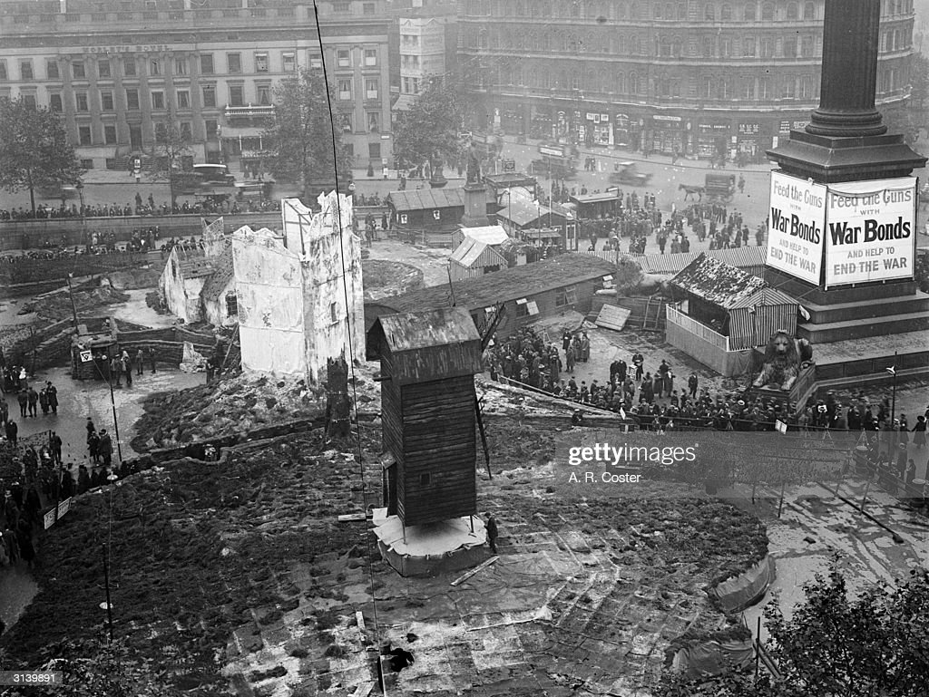 A sign round the base of Nelson's column encourages people to buy War Bonds at the 'Feed the Guns' campaign held in Trafalgar Square London...