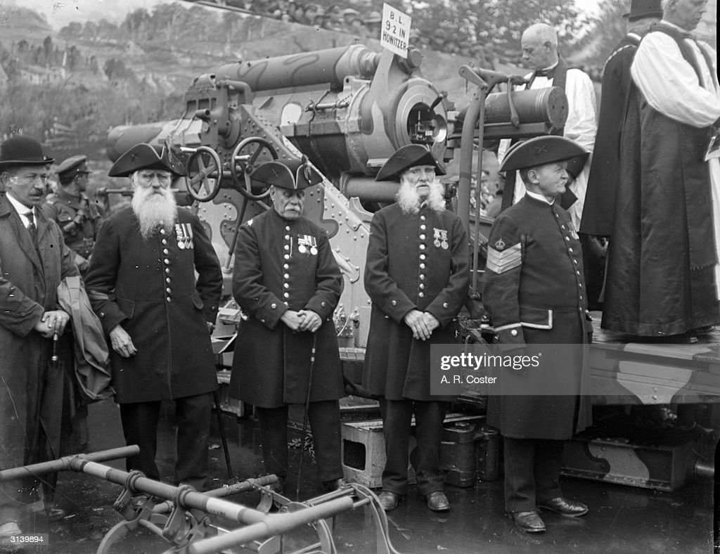 Chelsea Pensioners wearing their medals stand in front of a howitzer gun at a 'Feed the Guns' campaign in Trafalgar Square