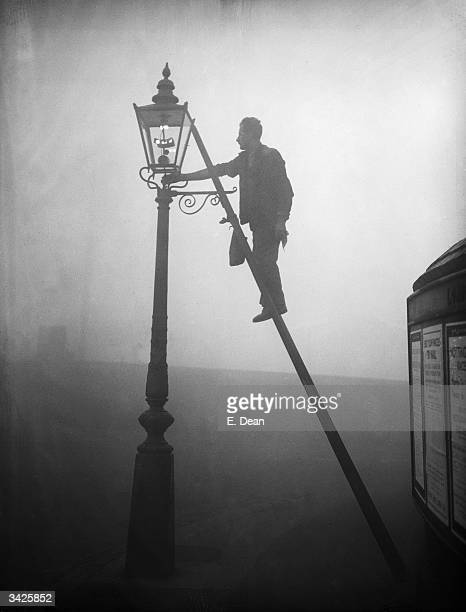 A lamp lighter at work in Finsbury Park London