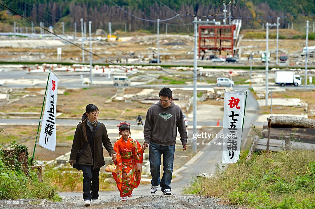 7-year-old Nanami Miura, dressed in traditional kimono, walk with her parent Shinya Miura (33) and Fumi Miura (34) to visit the Kaminoyama Shrine to mark the Shichi-Go-San on November 11, 2012 in Minamisanriku, Miyagi, Japan. Families have seven and three years old girls and five years old boys visit shrines for praying good health. Japan marks 20 months anniversary of the Great East Japan earthquake and following tsunami, occurred on March 11, 2011.