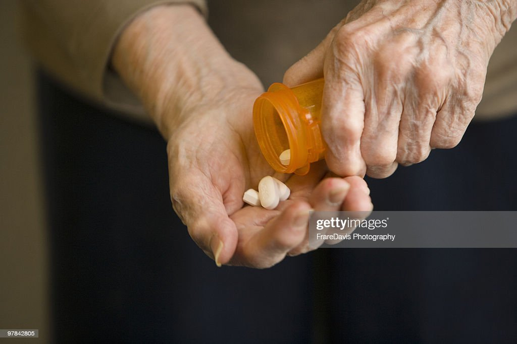 80-plus year old hands holding pills : Stock Photo