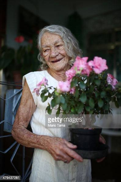 80yearold Maria de Lourdes de Lima a 40year Mare resident stands with flowers while posing in the unpacified Complexo da Mare slum complex one of the...