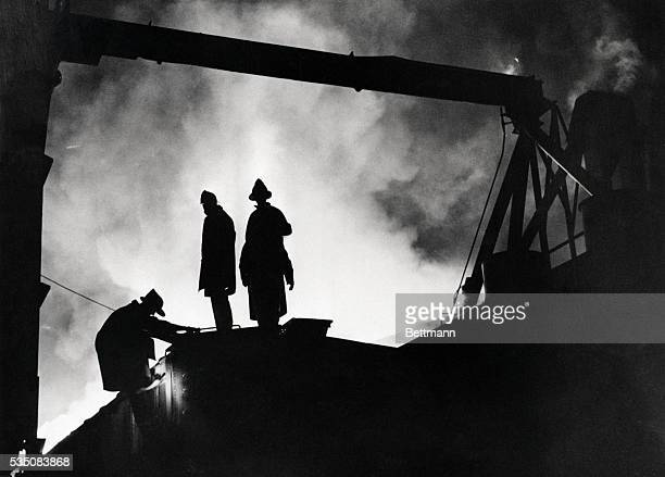 8/11/1968Chicago Heights IL Firemen are silhouetted against flames and smoke as they climb on railroad boxcar on siding to battle blaze in a Chicago...