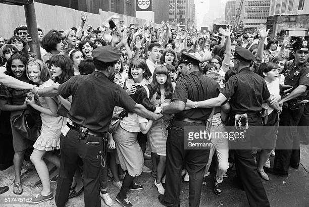 8/13/1965New York NY New York City policemen try to restrain hordes of teenagers mostly of the female variety from crashing into the Warwick Hotel...
