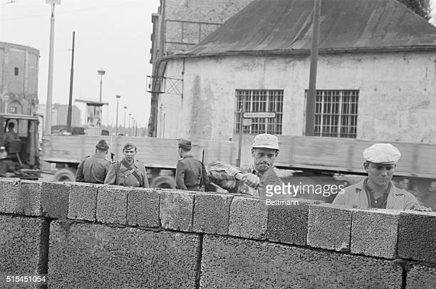 8/18/1961Berlin Germany Grimfaced East German workers under the watchful eyes of the Communist police erect a high concrete wall at a sector border...