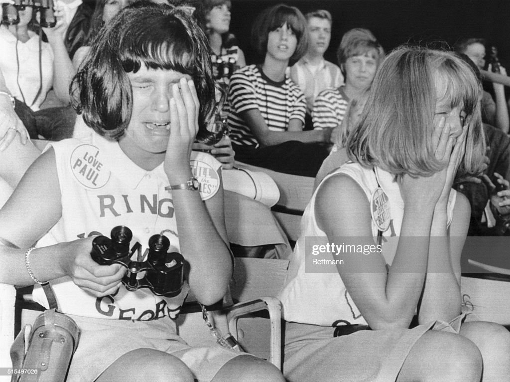 Chicago, IL- While thousands screamed, these two Beatles fans sobbed their hearts out during an afternoon appearance of the British rock and roll performers at Comiskey Park here 8/20. About 20,000 fans were on hand for the early performance.
