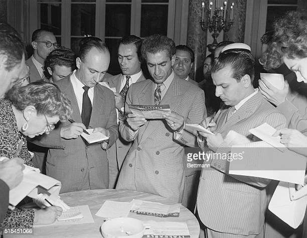 8/22/1953Rome Italy Shah Mohammed Reza Pahlevi is flanked by reporters as he reads a telegram urging him to return to Tehran After five days in exile...
