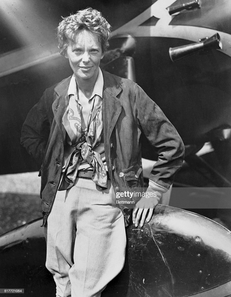 Mrs. Amelia Earhart Putnam, first woman to solo across the Atlantic, became the first woman to make a solo nonstop transcontinental flight when she landed at Newark, New Jersey, just a little over nineteen hours after she had left Los Angeles. Photo shows Miss Earhart Putnam leaning on her plane wheel well.