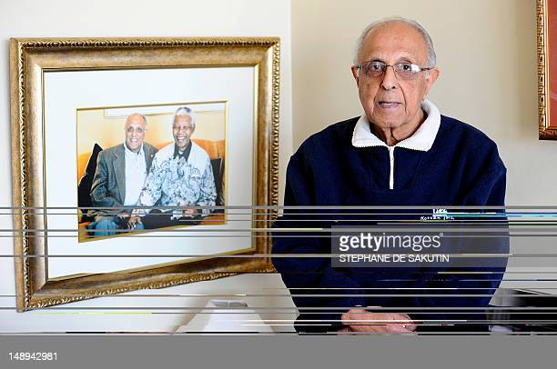 RENAUD 82yearold Ahmed Kathrada antiapartheid activist and close friend of former South African President Nelson Mandela poses next to a picture of...