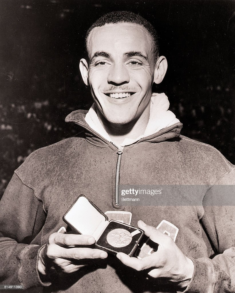 London, England- Mal Whitfield of the US displays his Gold Medal after setting a new Olympic record of 1 minute 49.2 seconds in the Men's 80-meter run at Empire Stadium.