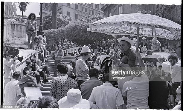 8/4/1971Rome ItalyFamed Italian film director Federico Fellini stands shaded from the hot Roman sun here as he gives instructions to his crew and the...