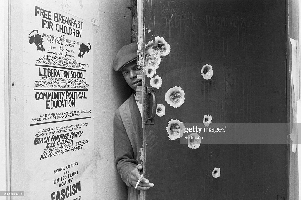 8/5/1969Chicago IL An unidentified member of the militant Black Panthers peeks around a bullet pocked door which police blasted with gunfire early...