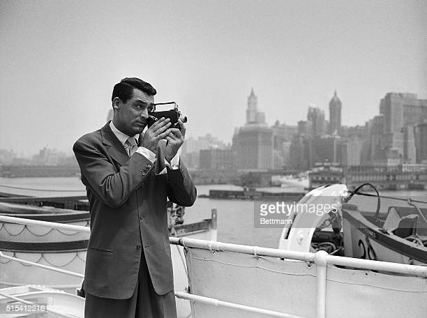 8/7/1938New York NY Returning from a vacation in Europe Cary Grant strong silent man of the movies takes pot shots with his camera at the New York...