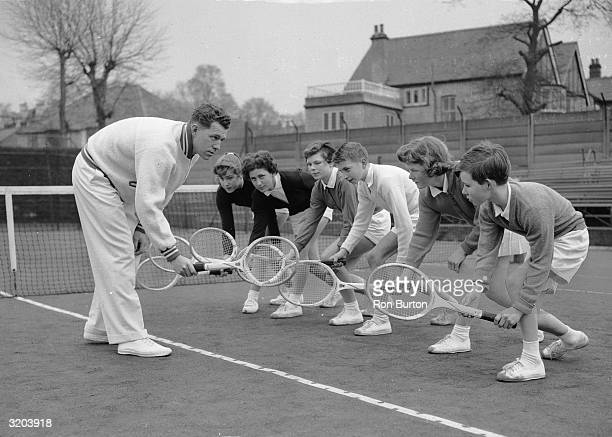 Australian chief tennis coach George Worthington demonstrates a stroke at Wimbledon to Hugh Pearman Toppy Anstey Stanley Mathews Rita Stone Janet...