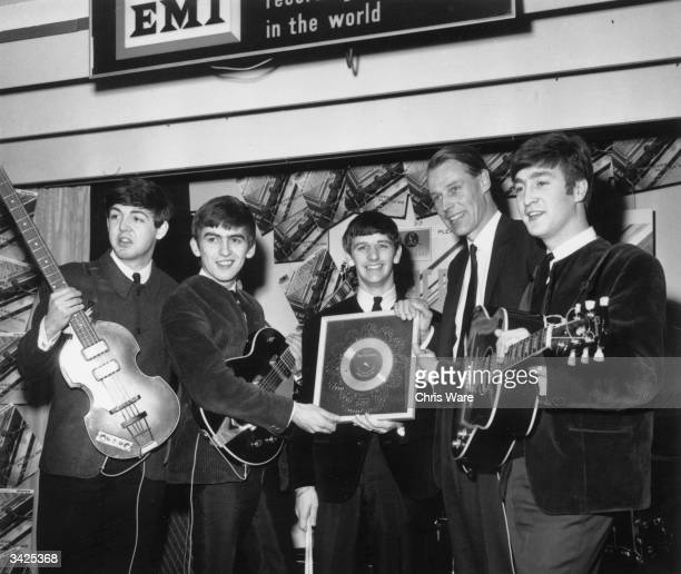 British pop group The Beatles holding their silver disc Left to right are Paul McCartney George Harrison Ringo Starr George Martin of EMI and John...