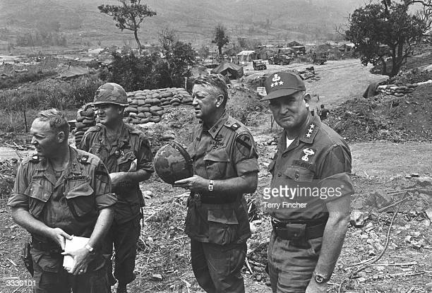 General Rosson and General John Tolson and two of their men survey the scene from a command post stand during the Vietnam war