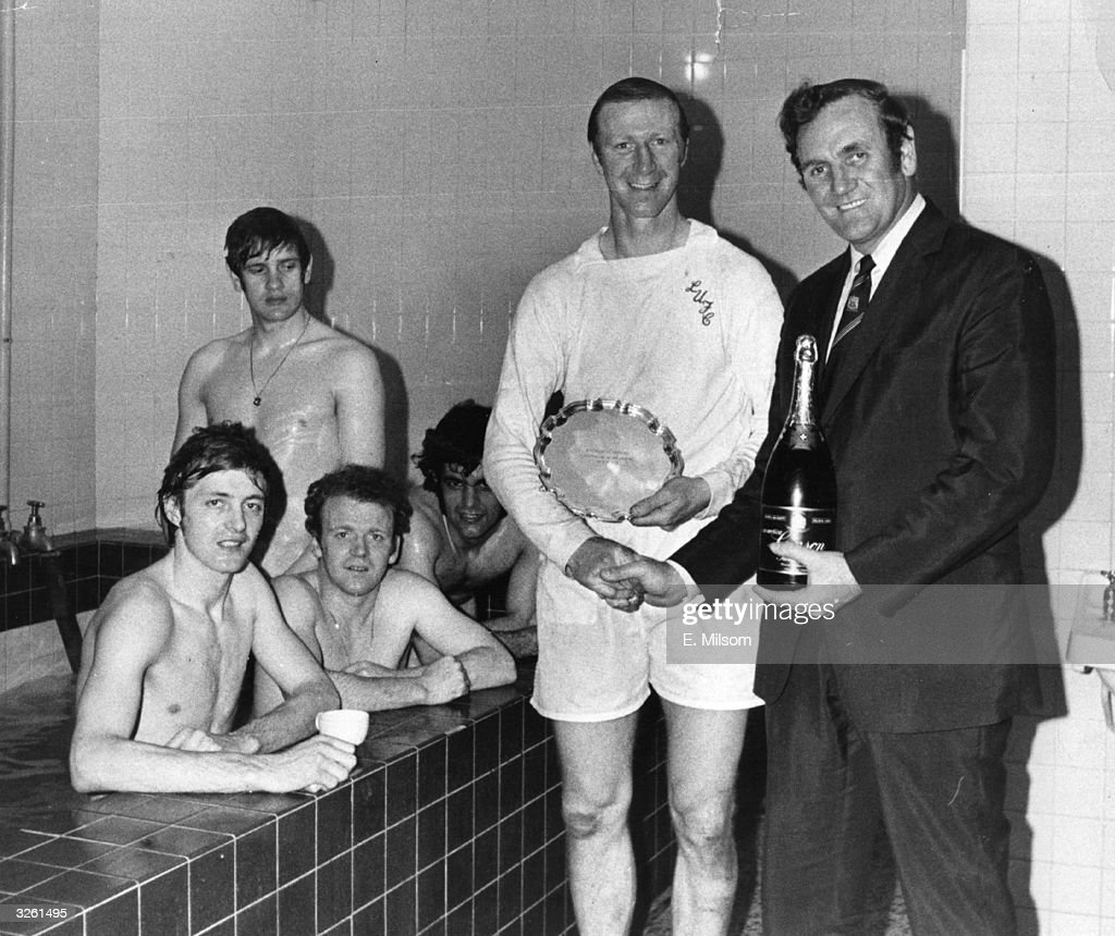 Leeds United manager Don Revie presents Jack Charlton with a bottle of champagne and the Footballer of the Month trophy in the changing room after a match. In the bath behind them are fellow Leeds players Clark, Billy Bremner (1942 -1997), Bates, and Gary Sprake (standing).