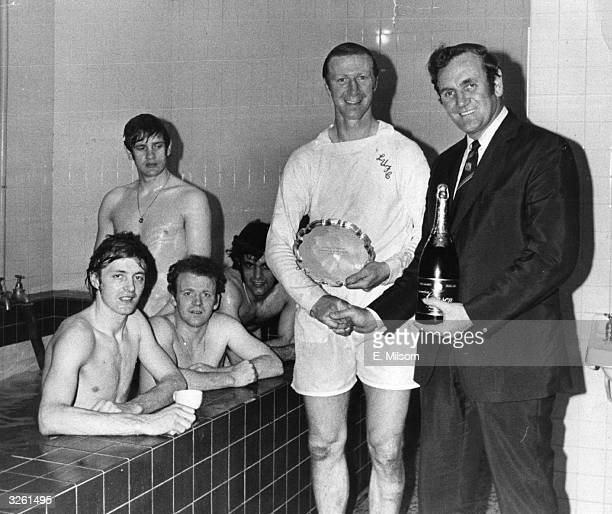 Leeds United manager Don Revie presents Jack Charlton with a bottle of champagne and the Footballer of the Month trophy in the changing room after a...