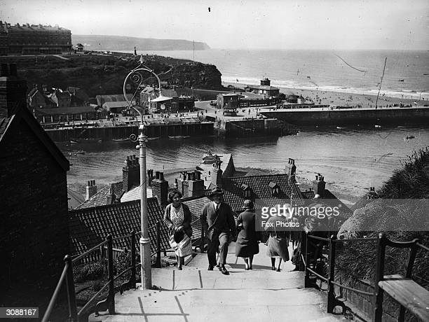 Visitors climb the 199 steps at Whitby in Yorkshire to get a better view of the town