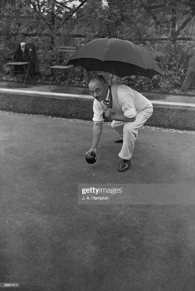 Kettering Conservative Club bowler ST Smith shelters under an umbrella whilst playing in a martch against High Wycombe at the Single Rink...