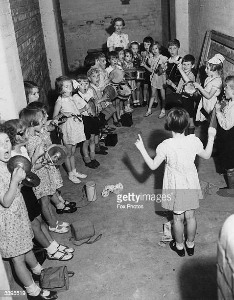 Members of the Wilbraham Infants School percussion band practising in a shelter during an air raid in Manchester The idea is to entertain the...
