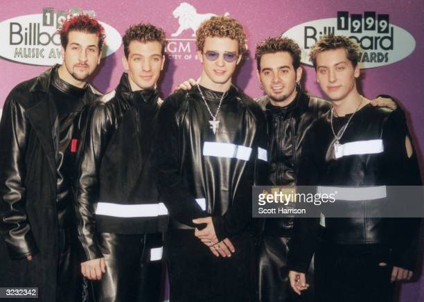American pop group 'N Sync wearing matching black leather outfits posing in front of a wall of logos at the 1999 Billboard Music Awards MGM Grand...
