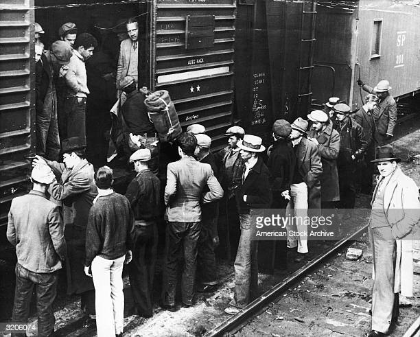 A large group of transient men is led back onto a train boxcar to send them away from Los Angeles California They had arrived in California by riding...