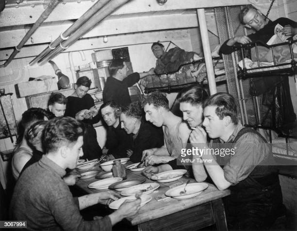 The crew of a British naval trawler relax in the ship's mess room some eating lunch some reading in their bunks The trawlers go out on daily patrols...