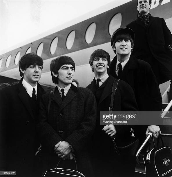 British pop phenomenon The Beatles standing on the steps of an aeroplane at London Airport Left to right Paul McCartney George Harrison Ringo Starr...