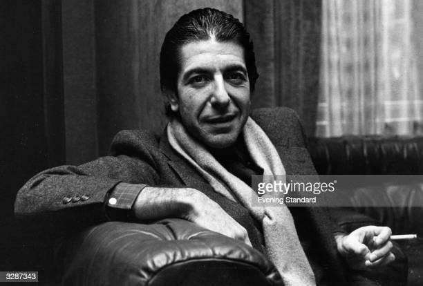 Solemn Canadian folk pop singersongwriter Leonard Cohen shares a joke and smokes a cigarette