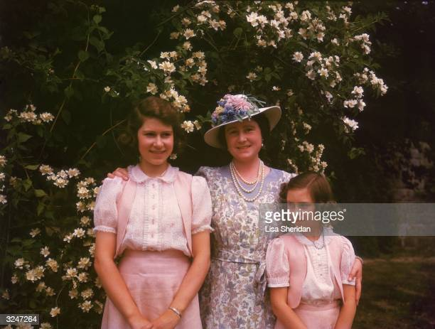 Queen Elizabeth with her daughters Princess Elizabeth and Princess Margaret by a syringa bush in the grounds of Windsor Castle Berkshire