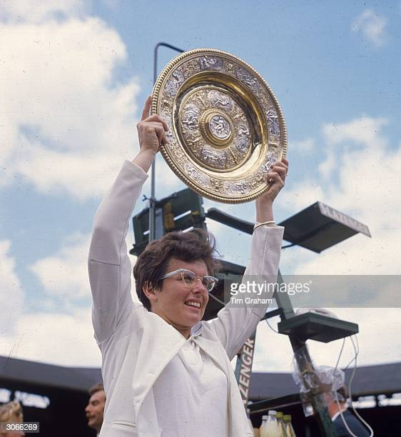 American tennis player Billie Jean King holds aloft the trophy after beating Ann Jones to win the women's singles title at the Wimbledon Lawn Tennis...