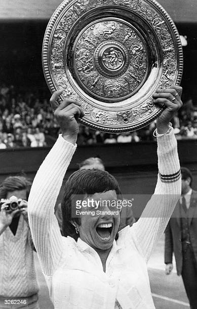 A jubilant Billie Jean King of the USA holds up the women's singles trophy at Wimbledon after winning it for the fourth time beating Evonne Goolagong