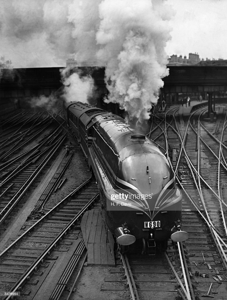 The new LMS streamlined locomotive 'Duchess of Gloucester' leaves Euston Station in London on her first long distance journey. She is transporting fifteen German railway experts to a summer meeting of the Institute of Locomotive Engineers in Glasgow.
