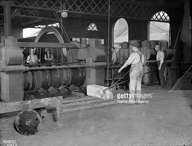 A heated ingot about to go through the rollers to be made into a rail at London and North Western Railway works Crewe Cheshire