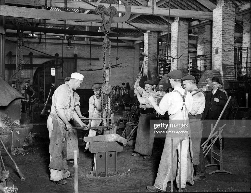 Workmen hammering a connecting rod at London and North Western Railway works Crewe Cheshire