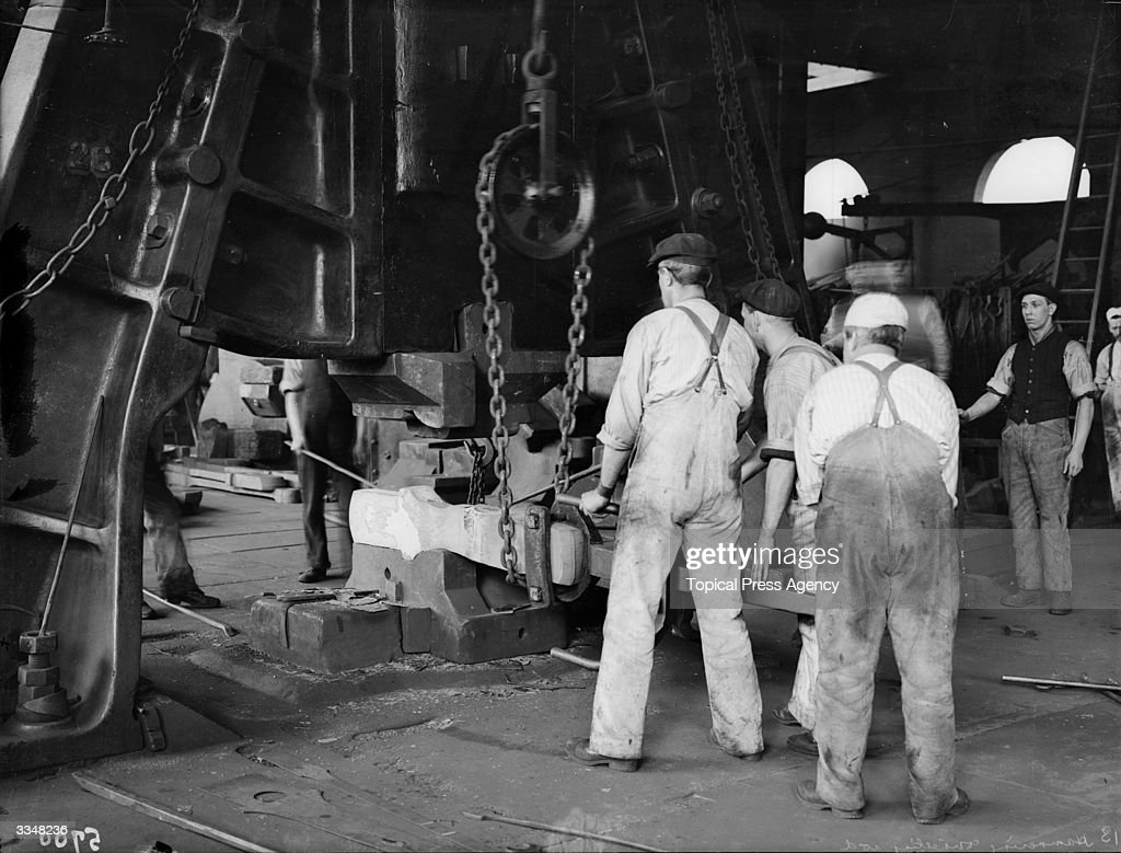 Workmen positioning a heated billet under a large press at the London and North Western Railway works Crewe Cheshire