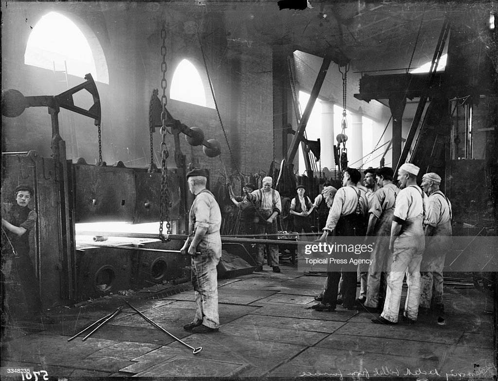Workmen removing a heated billet from the furnace at London and North Western Railway works Crewe Cheshire