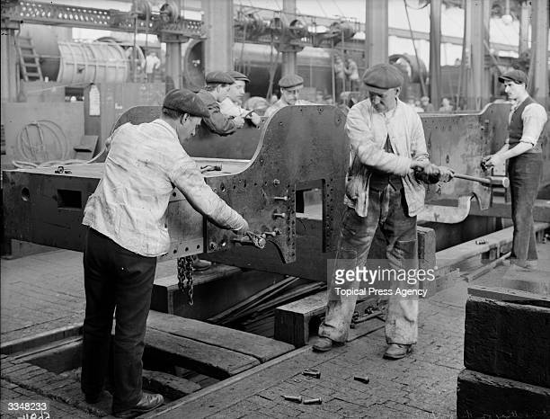 Workmen riveting the footplate of the Coronation Engine at the London and North Western Railway works at Crewe Cheshire