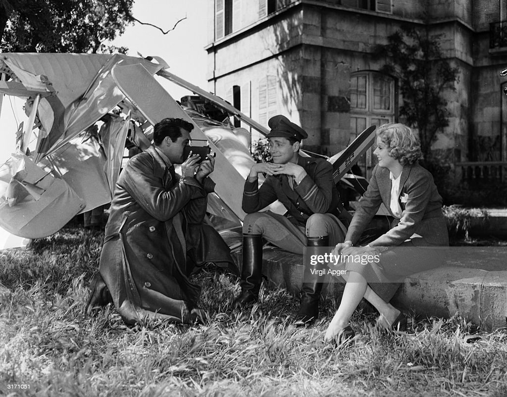 Cary Grant (1904 - 1986) films Jean Harlow and Franchot Tone during the making of 'Suzy' directed by George Fitzmaurice for MGM.