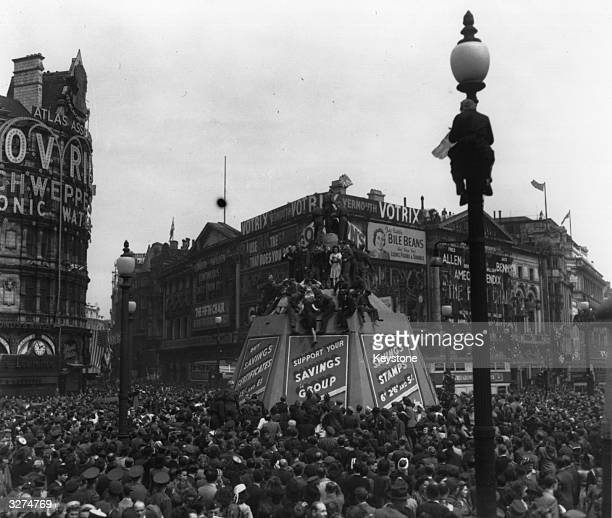 Crowds in Piccadilly Circus climb lampposts and the Eros statue's protective container on VE Day