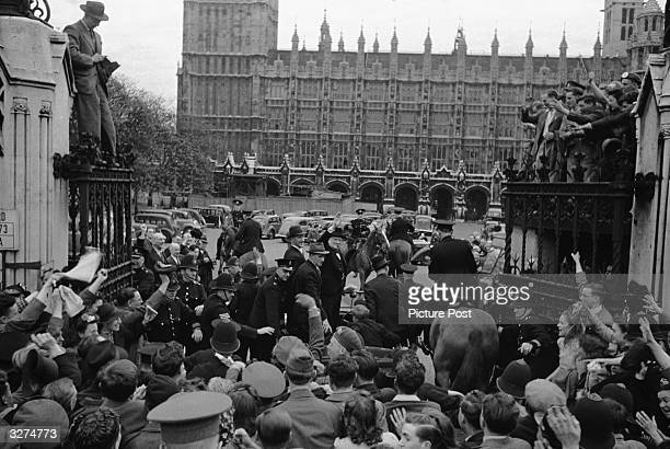 Prime Minister Winston Churchill waves to the excited crowds who have gathered outside the Houses of Parliament on VE Day Original Publication...