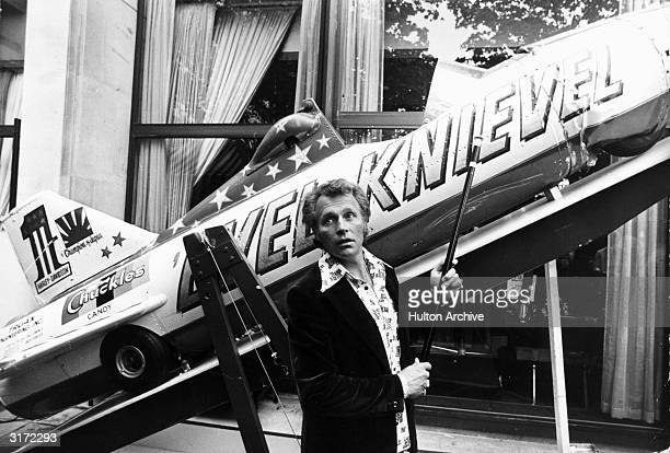 American stunt artist Evel Knievel points to his SkyCycle X2 plane which he used to jump across the Snake River Canyon in Idaho as he talks to...