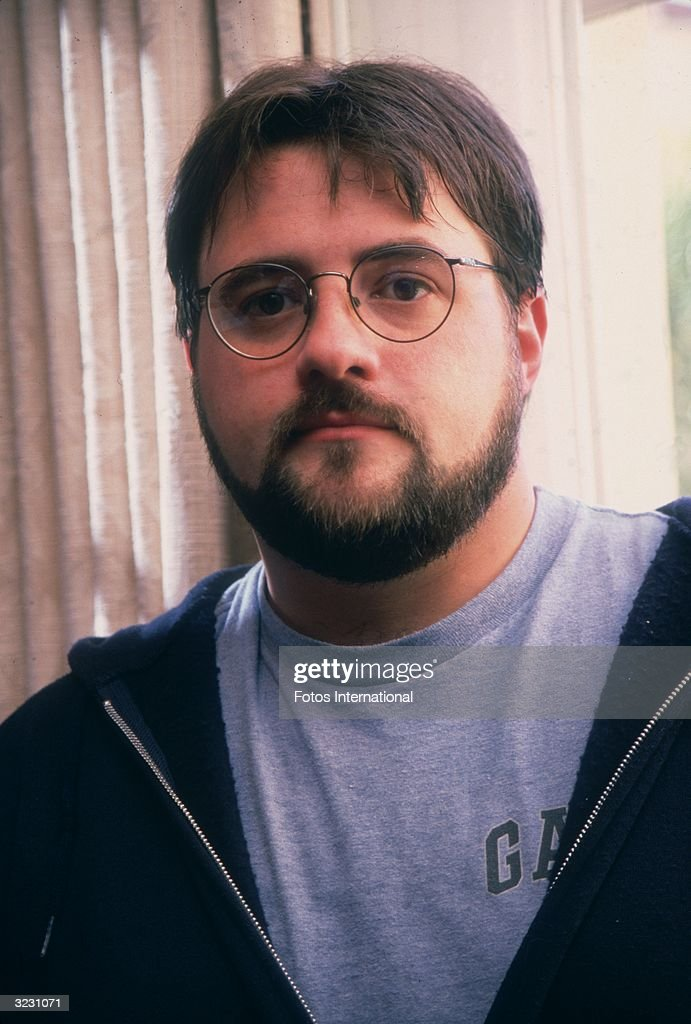 Headshot of American film director and screenwriter Kevin Smith wearing a gray GAP T-shirt and a dark hooded sweatshirt in front of a window, Beverly Hills, California.