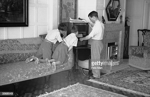 English jockey Gordon Richards listening to the radio at his home in Shoreham West Sussex with his sons Peter and Jackie Original Publication Picture...