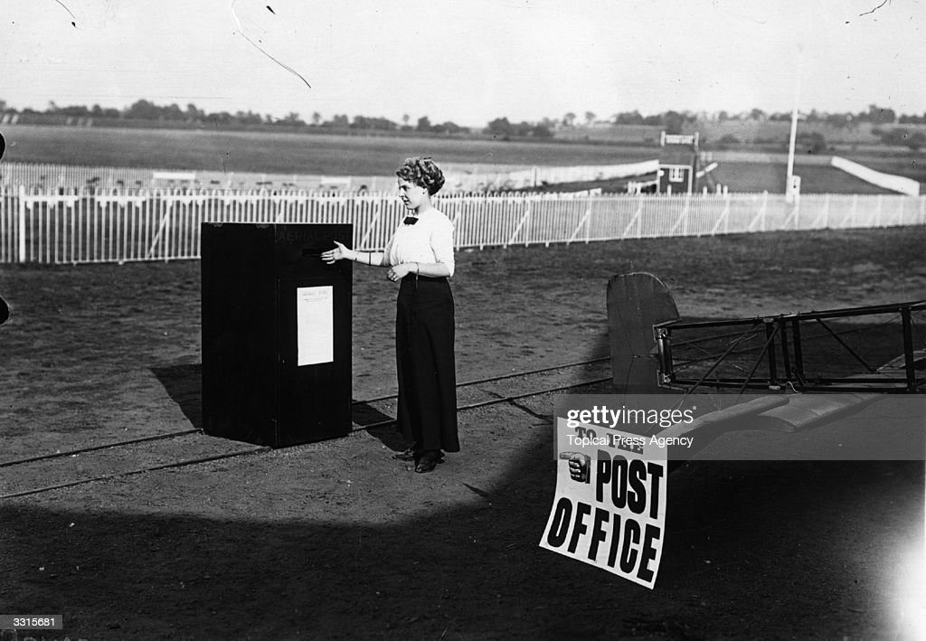 A young woman posts an aerial postcard at an aerodrome, for the new aerial postal service.