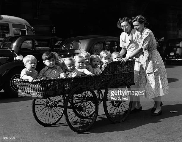 Ten babies from Coral Street Day Nursery on their morning outing in a long basketwork pram