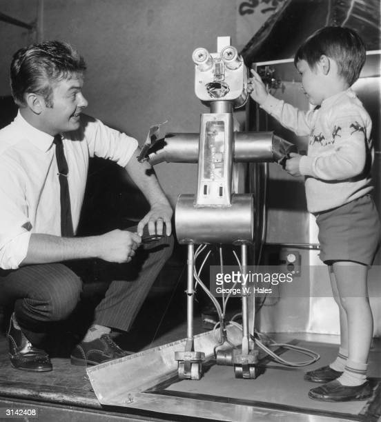 Four year old Stephen Clements inspecting Robby the Robot as its inventor Bernard Holling looks on Bernard a Sunday School teacher invented the robot...
